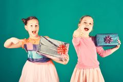 Girls with excited faces pose with presents on green background. New Year presents concept. Sisters with wrapped gift boxes for holiday. Children open gifts royalty free stock images