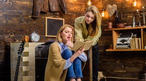 Girls excited about new work by favorite writer, literature discussion club, poetry night. Bookworms, mother and. Daughter, reading fascinating book in living Stock Photo