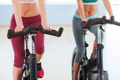 Girls on exercise bikes. Stock Photography