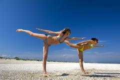 Girls exercising on a beach Stock Photos