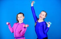 Girls exercising with dumbbells. Beginner dumbbells exercises. Children hold dumbbells blue background. Sport for teens stock photography