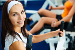 Girls exercising in gym. Portrait of girl exercising in gym. other girl on multi gym out of focus on background Stock Photography