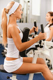 Girls exercising in gym. Portrait of two girls exercising in gym on various machines Stock Photo