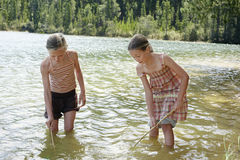 Girls Exploring Bottom Of Lake With Sticks Royalty Free Stock Image
