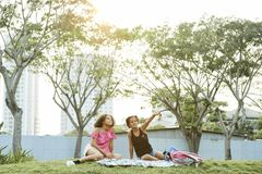 Girls exploring surrounding world. Curious pretty black girls in casual outfits sitting on blanket in city park and exploring surrounding world, braided girl stock photography
