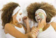 Girls with face masks. Happy women lying on towel putting puryfing mask Stock Photos