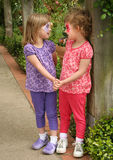Girls with Faces Painted. Two little girls hold hands and look at each other at a park after getting their faces painted Stock Photos