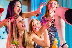 Girls with fancy cocktails in strip club. Drunk girls with fancy cocktails in strip club Royalty Free Stock Image