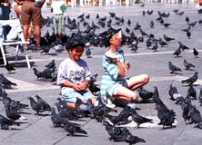 Girls feeding pigeons, Venice. Royalty Free Stock Image