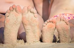 Girls feet on the beach. Close up of a feet of a mother and her little daughter girl sitting together on the beach in summer royalty free stock photography