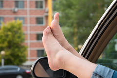 Girls feet. On the car window Stock Image