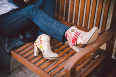 Girls feet in leather boots beige with embroidery on a wooden bench. Lookbook girls feet in leather boots beige with embroidery on a wooden bench Royalty Free Stock Photography