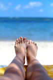 Girls feet in the sand on the background of the ocean. Girls feet in the sand Royalty Free Stock Images