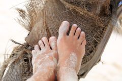 Girls feet in the sand on the palm tree Royalty Free Stock Photo