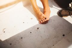 Girls feet without shoes with a pretty pedicure in the sunlight on the bright background of the old floor. The concept of a summer royalty free stock photo