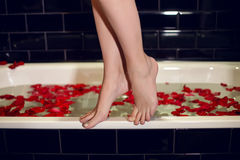 Girls feet standing on the edge of the white tubs Royalty Free Stock Image
