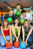 Girls and fellows stand with ball in bowling club. Three girls of squatting and three fellows  back stand with balls in bowling club, focus on girl in center Royalty Free Stock Photography