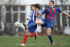 Girls fighting for ball during soccer game Stock Photo