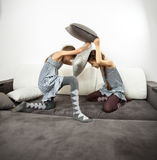 Girls fighting with cushions on couch Stock Image