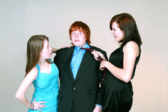 Girls fighting over blushing boy. Two caucasian teen girls fighting over blushing boy Royalty Free Stock Images