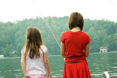 Girls Fishing/Early Morning. Two girls fishing in the early morning, the fog is lifting and maybe the fish will bite Royalty Free Stock Photo