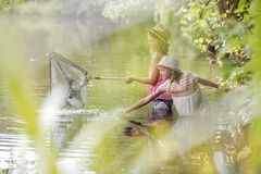 Girls fishing in lake by plants stock photo