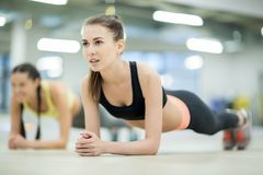 Girls in fitness center. Active girls doing planks on the floor of fitness club or at leisure center Stock Photo