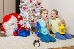 Girls with flashlights dreaming of gifts on New Years night, and Santa Claus put presents under the Christmas tree. Two girls with flashlights dreaming of gifts Royalty Free Stock Photography