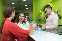 Girls flirting with barman. TTwo female friends flirting with handsome barman Stock Photo