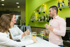 Girls flirting with barman Royalty Free Stock Photos