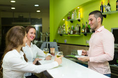 Girls flirting with barman Stock Images