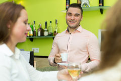 Girls flirting with barman Royalty Free Stock Image