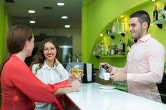Girls flirting with barman Stock Photography
