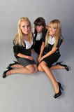 Girls on a floor. Three girls in corporate clothes sit on a floor Stock Image