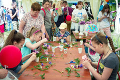 Girls at floristic workshop. Zaporizhia/Ukraine- May 28, 2017: Charity Family festival:  teen girls participating at floristic workshop, learning to arrange Royalty Free Stock Photo