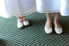 Girls focus on shoes. Loving shot of two young girls possibly on wedding day or first communion.. a celebration of any soft. Conveys sisterhood, friendship, love stock photography