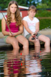 Girls focused on fishing floats Royalty Free Stock Photo