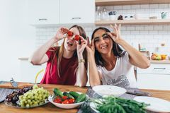 Girls fooling around in the kitchen playing with vegetables. Girls fooling around in the kitchen playing with vegetables Royalty Free Stock Photos