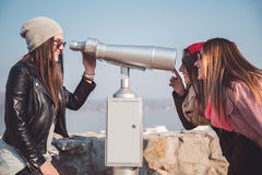 Girls fooling around with panorama binoculars. Telescope Stock Image