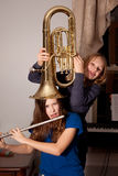 Girls fooling with musical instruments Royalty Free Stock Photography