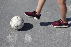Girls football. Girls` football, girls` soccer, ball, legs and sneakers, asphalt playground Royalty Free Stock Photography