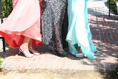 Girls in formal dresses with shoes. Girls dressed in formal dresses with close-up of shoes stock photo