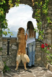 Girls friend. Young male golden retriever standing at his rear legs next to a girl, both looking over a balustrade Stock Photos