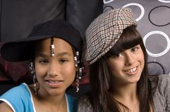 Girls friends. Cute african american girl and caucasian girl friend, both wearing hats Royalty Free Stock Photo