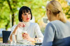 Girls friends drink coffee talk. Conversation women cafe terrace. Friendship friendly relations. Discussing rumors. Trustful communication. Friendship sisters stock image