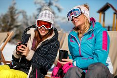 Girls friends enjoying hot drink in cafe at ski resort. Sunbathi. Happy girls friends enjoying hot drink in cafe at ski resort. Sunbathing in snow Royalty Free Stock Photography