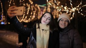 Girls friends making selfie photo at night alley decorated by garland. Girls friends making selfie photo at the night alley decorated by garland stock footage