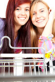 Girls friends with shopping cart Royalty Free Stock Images