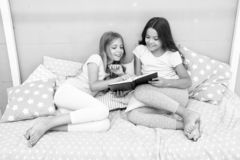 Girls friends or sisters lay bed read book together. Kids prepare go to bed. Pleasant time cozy bedroom. Girls long hair stock image