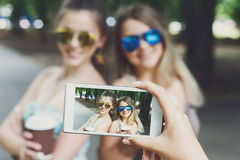 Girls friends taking photos with smartphone outdoors Stock Image